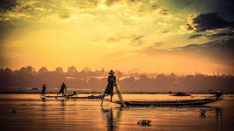 Myanmar travel attraction landmark - traditional Burmese fishermen sihouettes at Inle lake on sunset, Myanmar famous for their distinctive one legged rowing style