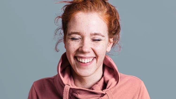 close-up-happy-woman-with-pink-hoodie-grey-background_cropped-16.jpg